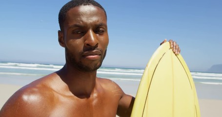0 19 Male surfer standing with surfboard at beach 4k 8575272f7