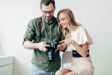 a pleasant photographer showing models the photos on his camera after an indoor photo shoot. close up photo