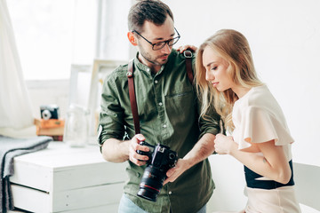 serious guy and girl having a problem with a camera, close up photo. broken tool, device, pleasant couple chimping in the room