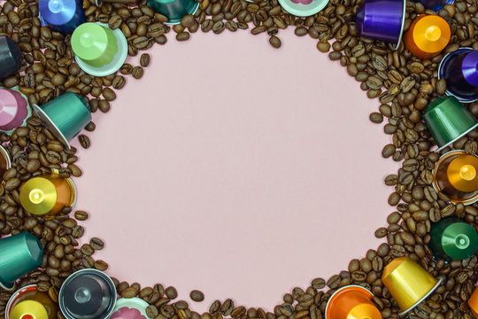 Multicolored coffee pod capsule on coffee beans close up. space for text