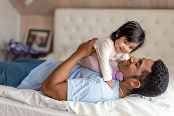 cheerful caring daddy enjoying time with a baby girl,close up side view photo