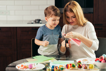 It is so funny to prepare to Holy Easter with children. Attractive blonde woman is teaching her adorable little kid how to cut out Easter decor from the coloured paper , sitting at kitchen