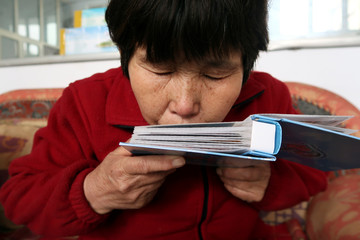 Liu Shuangfeng kisses an album with pictures of her son during a Reuters interview at her house in Handan