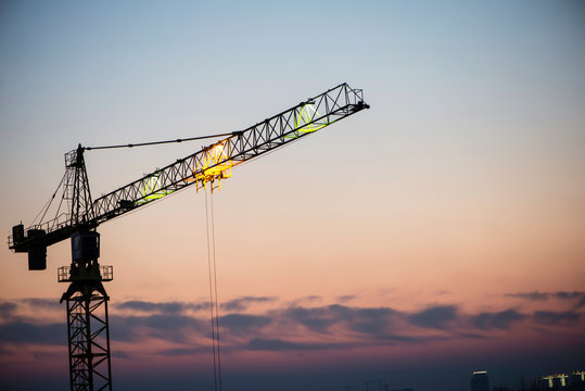 high-rise building crane on the background of the evening sky, building