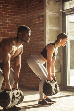 Diverse multiracial sports partners including workout with heavy sand bags in training program, get strength, speed, endurance, balance and mobility, which distinguishes modern strongmen-athletes.