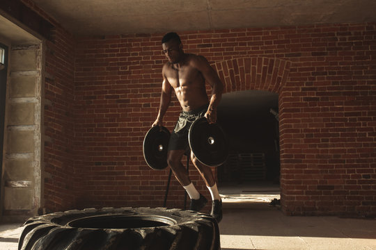 African american crossfit sportsmen holding barbell plates as weighting in both hands making jumps on big rubber wheel, lying on the floor of street local gym.