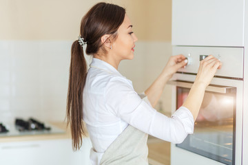 cheerful Asian girl turning on the oven in the kitchen. close up side view photo. chef has put the dish in the oven to preheat it