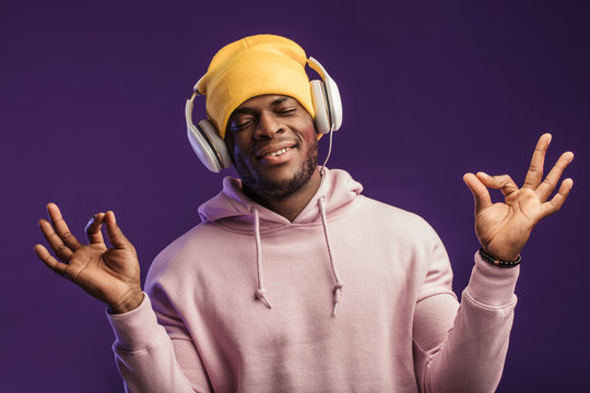 Studio portrait of handsome satisfied young man of African ethnicity and headphones, enjoying listening to buddhist mantras, keeping fingers in mudra gesture
