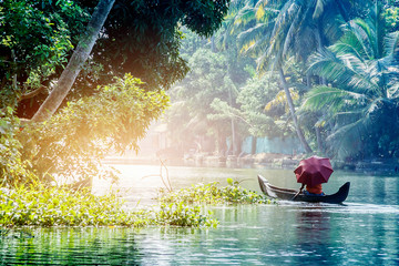 A man with an umbrella in a traditional boat sails through the backwaters of Alleppey in Kerala, South India. ALAPPUZHA KERALA Wall mural
