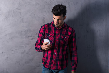 A smiling young man using his smartphone in a red shirt