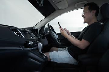 Asian man driver using smart phone in car .