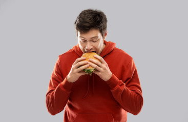 fast food and people concept - hungry young man in red hoodie eating hamburger over grey background