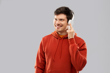 music, technology and people concept - happy young man in headphones and red hoodie over grey background