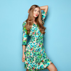 Blonde Young Woman in Floral Spring Summer Dress. Girl Posing on a Blue Background. Summer Floral Outfit. Stylish Wavy Hairstyle. Fashion Photo. Blonde Lady