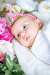 Newborn baby in a flower dressing lies in spring flowers