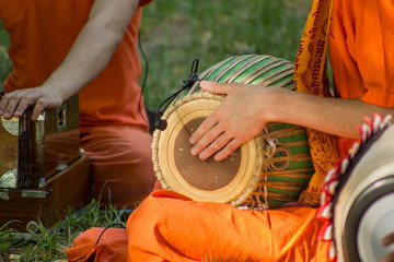 Harri Hare Krishna musicians in orange cloth playing on drum ethnic instrument close up