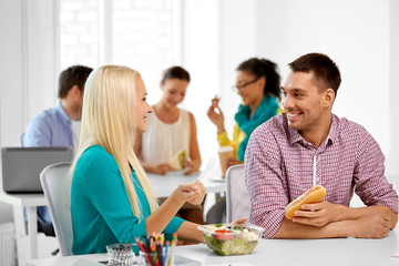 corporate, communication and people concept - happy colleagues having lunch and eating at office