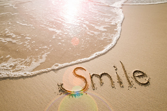 Smile message handwritten on the smooth sand of an empty beach with an oncoming wave and sunlight lens flare