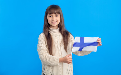 Little girl with flag of Finland on blue background. Learn Finnish. Schoolgirl studying abroad.