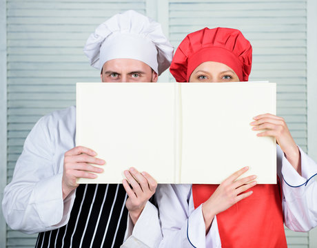 Book family recipes. Cooking guide. According to recipe. Manand woman chef hide faces behind open book. Guy and girl read book recipes. Culinary concept. Family learn recipe. Improve cooking skill