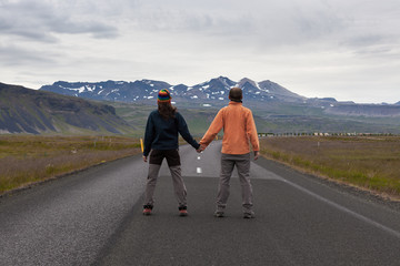 Iceland - Jul 19, 2016: Rear view of man and woman hikers standing on the empty road in Iceland. Mountains on the horizon. Couple of tourists holding hands. Hitchhiking in Icelandic nature landscape.