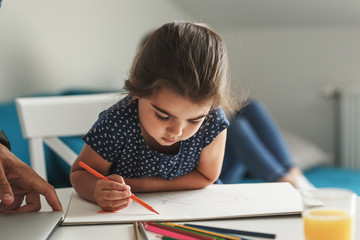 Little girl learn to draw with colored pencils.