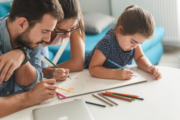 Father and mother teach daughter to draw.They sitting in living room.Education and family concept.