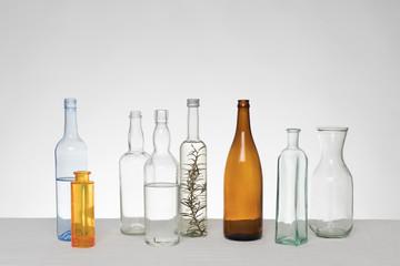 Verschiedene Glasflaschen vor weißem Hintergrund auf Tischdecke aus Leinen