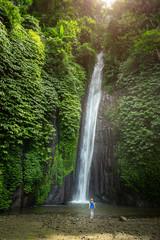 girl watching a waterfall in Bali Indonesia