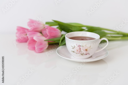 Morning tea with pink tulips on white table. Close up. Soft focus. Spring concept. Happy Mother's Day, Women's Day or Birthday. Minimalism, copy space.