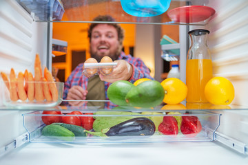 Man taking eggs from fridge to make a meal late at night. Unhealthy eating and eating disorder concept. Picture taken from the inside of fridge.