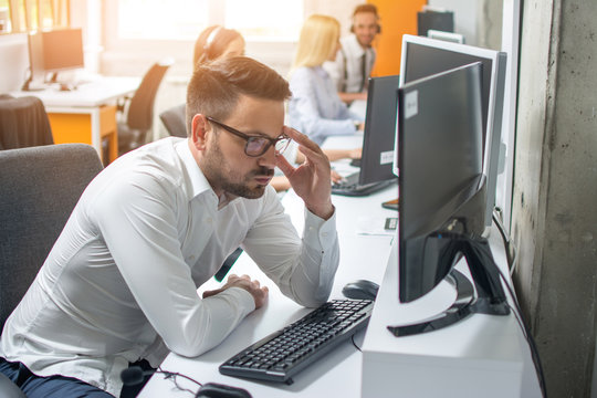 Worried businessman looking at computer screen at his workplace in office