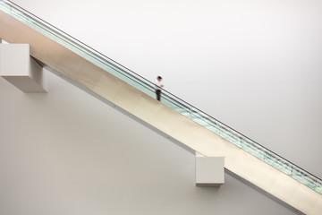 man rolling downwards on an escalator