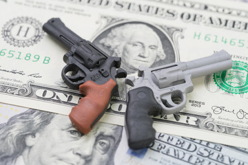 Big money in gun industry, gun control policy in united state of america concept, mass shooting protection, miniature toy guns on US dallar bill