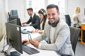 Portrait of smiling handsome businessman with headphones around neck and eyeglasses in hand looking at camera in the call center office