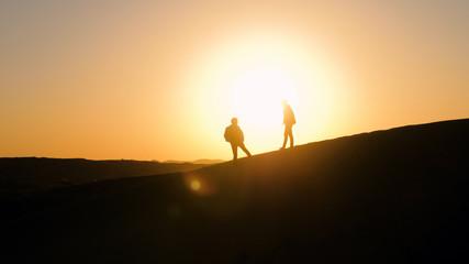 Silhouettes of men against sunset