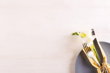 Table setting arrangement in minimal style with easter spring holiday attributes, fork, knife and napkin. Background, copy space, close up, flat lay, top view.