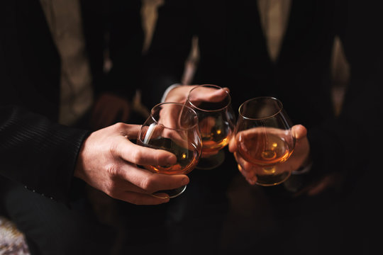 Business meeting. Men hold glasses of whiskey. Men's Party. Hand with a drink of alcohol