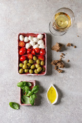Mozzarella, cherry tomatoes, olives antipasto appetizers served in pink ceramic rectangular plates with olive oil, glass of white wine, basil, rye bread over grey texture background. Flat lay, space