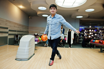 South asian man in jeans shirt standing at bowling alley with ball on hands. Guy is preparing for a throw.