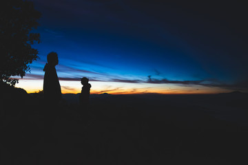 Two silhouette of people watching the sunrise on top of a mountain in northern part of Thailand.
