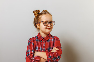 Portrait of a funny little preschool child girl in glasses on gray background. Education. Back to school. Wall mural