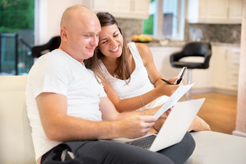 Young couple on the sofa with laptop and count the bill for payment. The concept of utilities, debt, people and credit. Family concept, family budget
