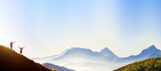 Small dark silhouettes of tourist travelers on steep mountain slope at sunrise on copy space background of valley covered with white puffy clouds and bright clear sky. Fototapete