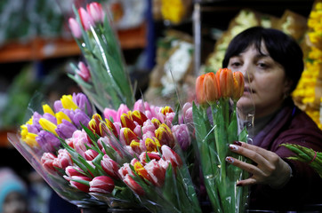 An employee places a bouquet at a flower market ahead of International Women's Day in Moscow