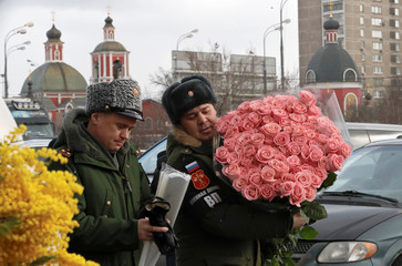 An officer holds a bunch of roses near a flower market ahead of International Women's Day in Moscow