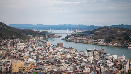 Panoramic, scenic view of Onomichi City and the Seto Inland Sea as seen while climbing the countless steps towards the summit of Mt. Senkoji in Hiroshima Prefecture in Japan.