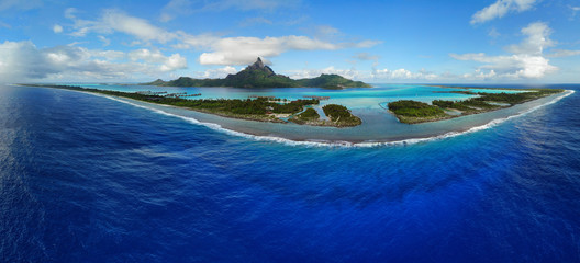 Aerial panoramic landscape view of the island of Bora Bora in French Polynesia with the Mont Otemanu mountain surrounded by a turquoise lagoon, motu atolls, reef barrier, and the South Pacific Ocean Wall mural