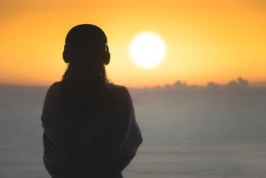 Silhouette of naked woman with wet hair wrapped in a blanket after swimming. Female in the headphones standing on the beach opposite sea.