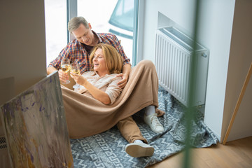 happy couple clinking glasses while resting on floor by large window at new home